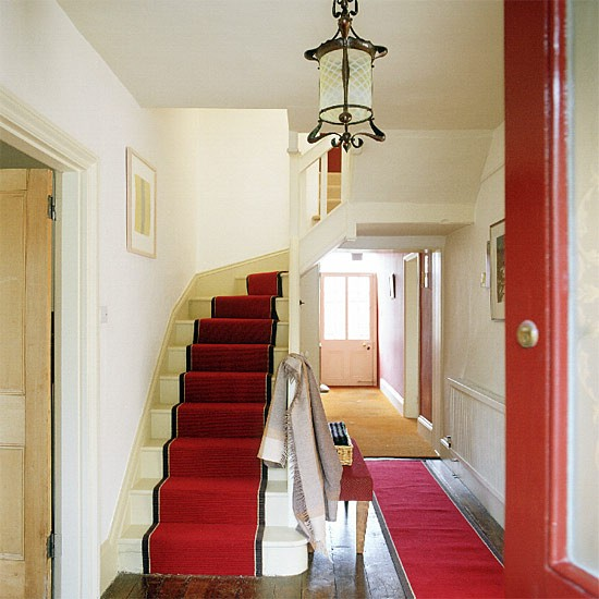 Hallway With Red Carpet, Curving Stairs And Antique Light