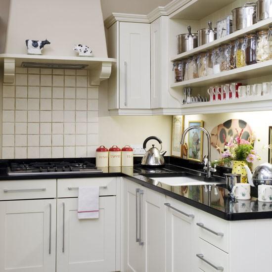small kitchen with white cabinetry white splashback tiles and black granite worktop - Open Shelves Kitchen Design Ideas