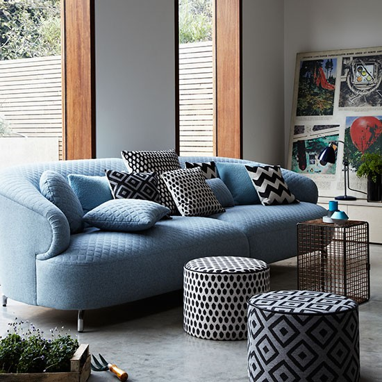 Modern Living Room With Blue Sofa And Poufs