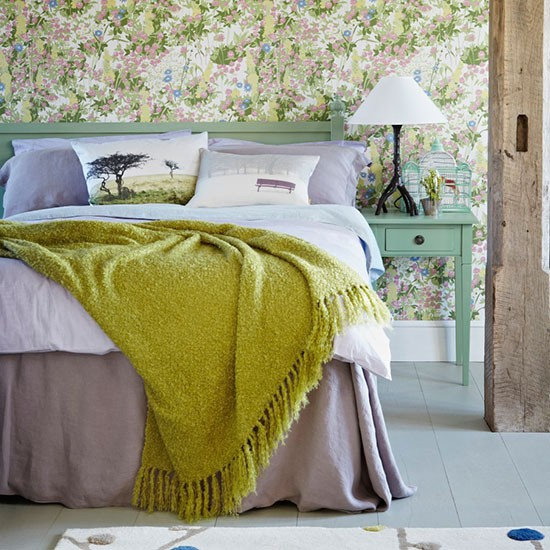 Country bedroom with pastel bedlinen and floral wallpaper ...