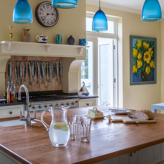 Yellow Kitchen With Blue Pendant Lighting And Island